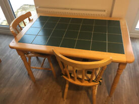 Solid pine table with green tiled top and two chairs