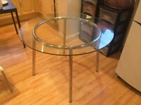 A Round Glass Dining Table with Chrome Legs