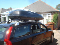 Large car topbox with crossbars to fit standard roof rails.