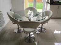 Round glass table and four leather chairs