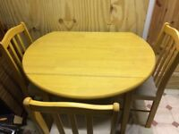 Light wood round dining room table and three chairs