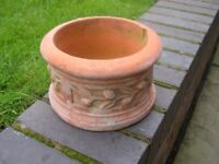 A round terracotta planter with side decoration.