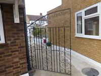 a pair of wrought iron black metal gates