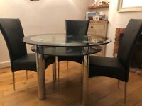 Harvey's round glass table and 4 black faux leather chairs