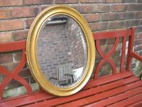 A vintage alabater on wood framed oval mirror with bevelled edges.