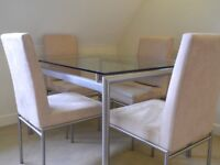 Beautiful solid glass dining table with 4 light cream suede chairs