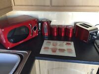 Red kettle, toaster, microwave and tea coffee and sugar pots