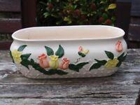 White ceramic planter with flower decoration