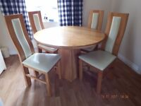 Solid oak round dining table and four chairs