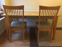 Light wood dining table and six chairs with metal accents and off-white upholstery