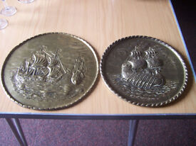 pair of brass plates displaying ships