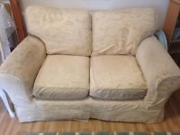 Two seater sofa with cream patterned removable fabric cover