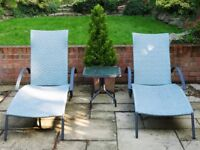 Pair of grey rattan sun loungers and matching table