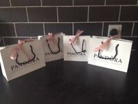 Four Pandora gift bags, four charm boxes and a bracelet box