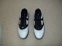 Mens golf shoes two pair one black one white.