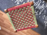 small wooden stool with woven top.
