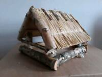 Birch wood bird house covered with straw