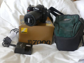 Nikon D7000 digital camera together with charger, case, spare battery and operating instructions.