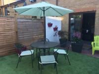 Garden table, 4 chairs with cushions, parasol and base