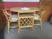 Cane table and chairs with seat cushions, excellent condition.