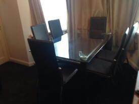 tampered glass top dining table with a leather shelf and covered legs in leather with 6 chairs