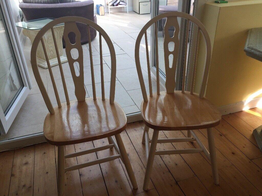 Pair of kitchen chairs. Wooden with cream backs and legs. Detailed back. Chairs
