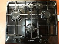 Gas hob with 4 large to small sized burners. Hotpoint, dark brown colour.