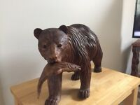 Beautifully carved dark wooden bear with a fish in its mouth