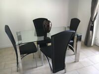 Glass table with silver legs and four black leather chairs. Rarely used and was bought for £750