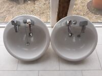 White porcelain round sinks with Chrome taps and waste