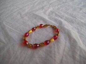 Bracelet with red cristal beads and golden metal beads