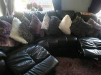 Large reclining black curved sofa with storage pouffe.