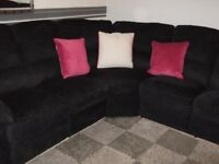 Black fabric sofa corner suite with recliners on both ends, in good condition