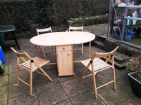 Table with 2 folding drop-leaves. Pull-out drawers. 4 folding chairs.