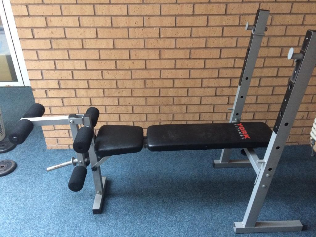Weight bench with rack and leg extension. Weight plates and free weights.