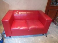 Small red leather 2 seater settee.