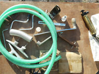 An assortment of boat bits, including an oil pump, tubing, a pair of strong aluminium cleats