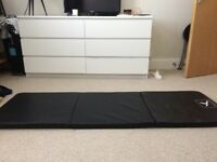 Folding gym/yoga mat with carry hankle
