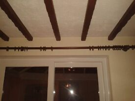 Solid mahogany curtain rail with finials and rings. 240cm in length, 3.5cm in diameter
