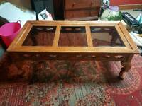 Carved wood coffee table with smoked glass inserts