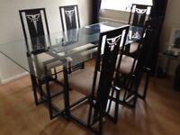 Dark grey metal and glass dining table and six chairs.