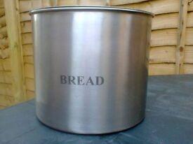 A Stainless steel breadbin measuring 24cm high.