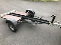 Motorcycle trailer by Dave Cooper with side bars and added floor boards, in good condition