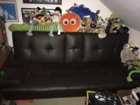 Brown leather sofa bed with pull down arm rest and cup holders