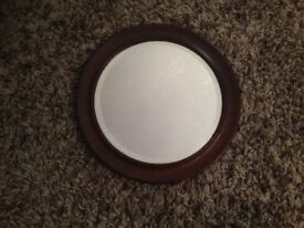 LOVELY SMALL ROUND MIRROR IN BROWN OAK FRAME .