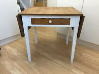 Wooden drop-leaf table with white legs and a drawer