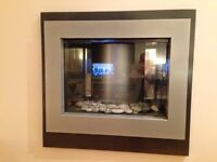 Contemporary black/silver wall mounted electric fire virtual flame effect with real pebbles in