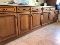 Fitted wood kitchen with multiple cupboards and drawers