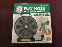Flat hose with spray nozzle