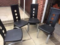 Four black leather dining chairs